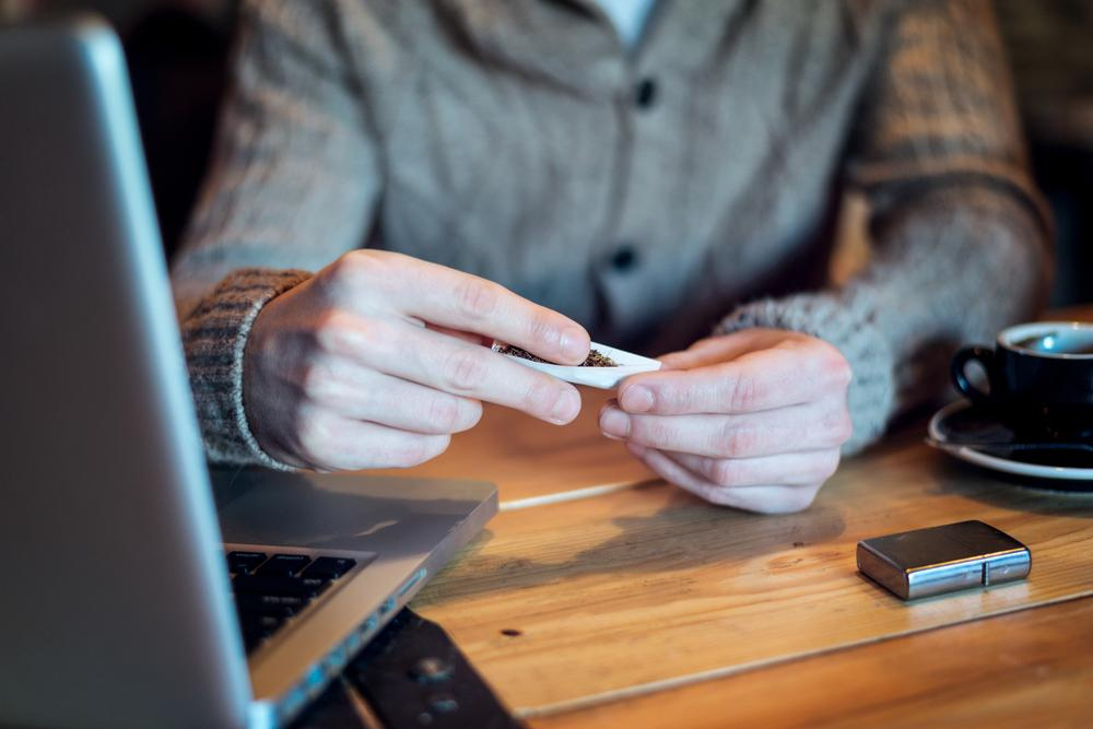 man rolling joint on his desk next to computer and cup of coffee